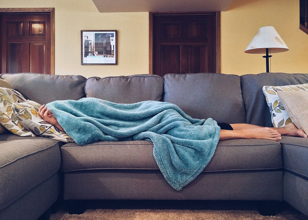 Person lying on couch with adrenal fatigue