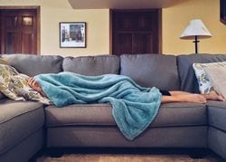 Person lying on couch due to Adrenal Fatigue