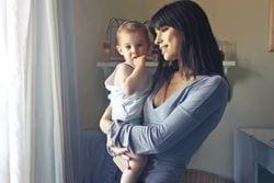 Woman who looks like she has hormonal imbalances holding a baby