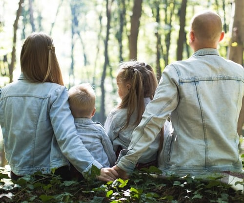 family with back turned in forest